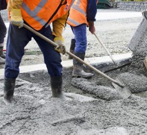 Three Construction Workers Moving Concrete