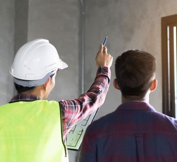 Man In A Hardhat Points at a Wall With A Pencil While Another Man Looks At The Wall