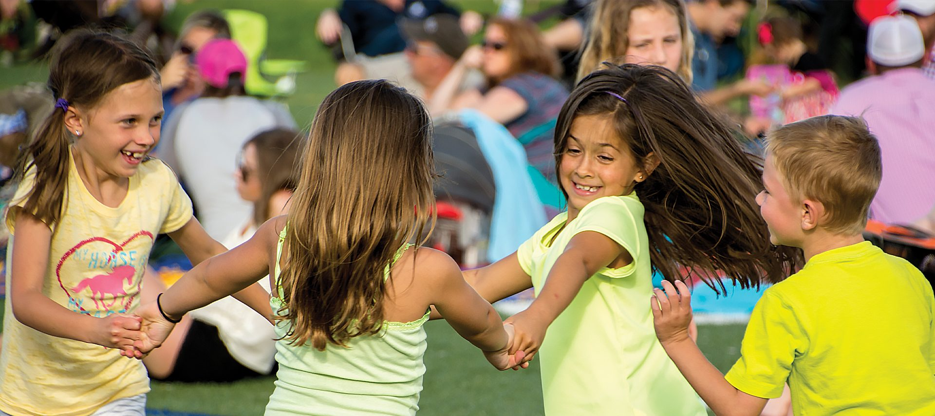 Kids dancing at an outdoor concert