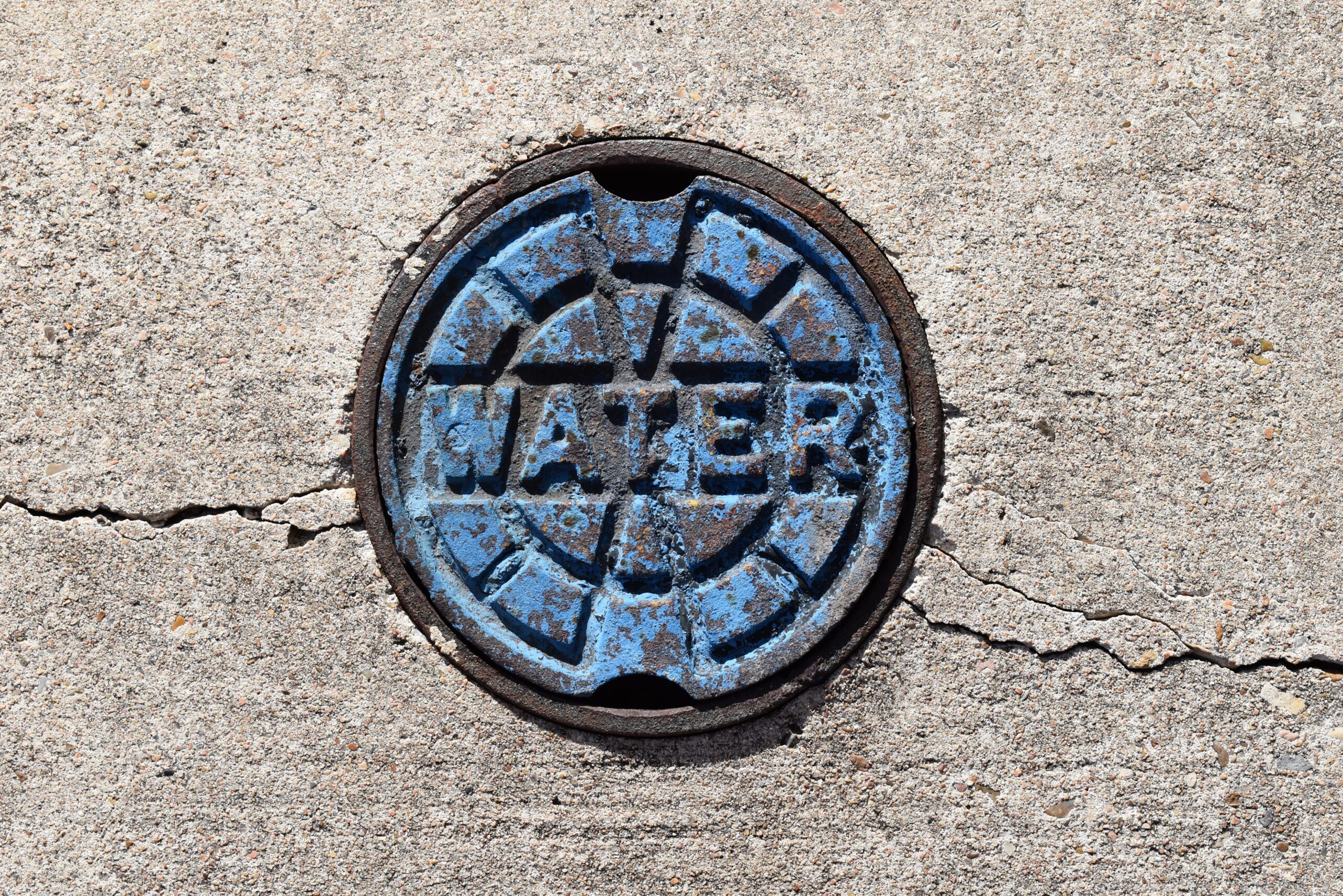 Photo by Greg Jewett on Unsplash. Water shutoff valve cover. Blue paint is starting to flake off.